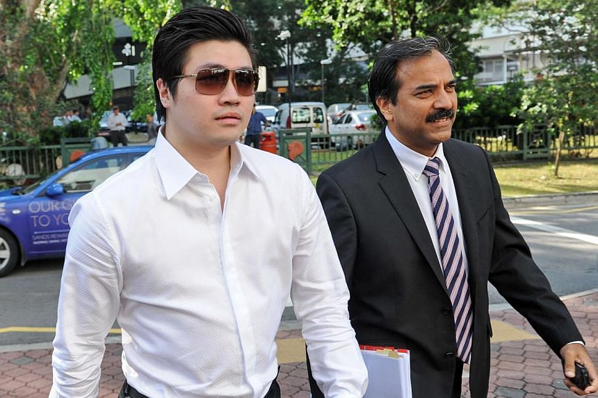 Singaporean businessman Eric Ding Si Yang (left) arrives at a district court with his lawyer in Singapore on Aug 27, 2013. The trial against alleged match-fixer Eric Ding Si Yang resumed Thursday with The New Paper editor Dominic Nathan taking the st