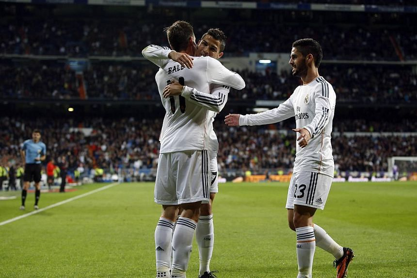 Real Madrid's Gareth Bale (left) celebrates scoring against Sevilla with teammates Cristiano Ronaldo and Isco (right) during their Spanish first division soccer match at Santiago Bernabeu stadium in Madrid on Oct 30, 2013. -- PHOTO: REUTERS