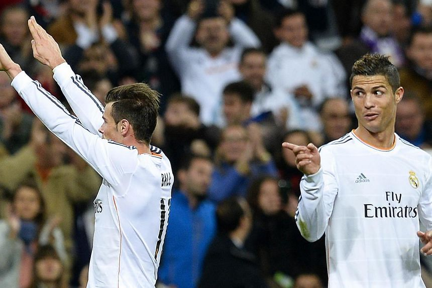 Real Madrid's Welsh striker Gareth Bale (left) celebrates after scoring his second goal next to Real Madrid's Portuguese forward Cristiano Ronaldo during the Spanish league football match Real Madrid CF v Sevilla FC at the Santiago Bernabeu stadium i