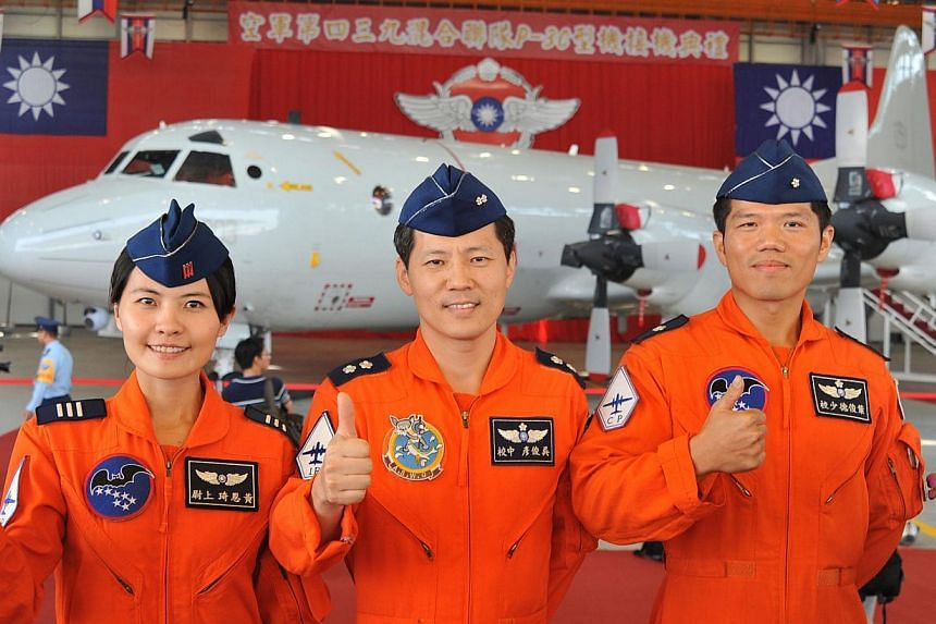 Three colonels pose for photos during a ceremony marking the receiving of the first P-3C Orion patrol aircraft at an air force base in Pingtung, southern Taiwan, on Oct 31, 2013. Taiwan displayed its first long-range submarine-hunting aircraft, days