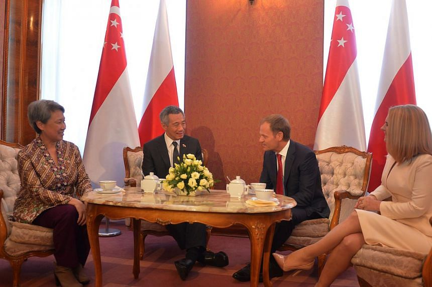 Prime Minister Lee Hsien Loong and Mrs Lee chat in the Clock Room at the Chancellery of the Prime Minister with Polish Prime Minister Donald Tusk and his wife, Mrs Malgorzata Tusk, after the welcome ceremony, on Oct 31, 2013. -- ST PHOTO: CAROLINE CH