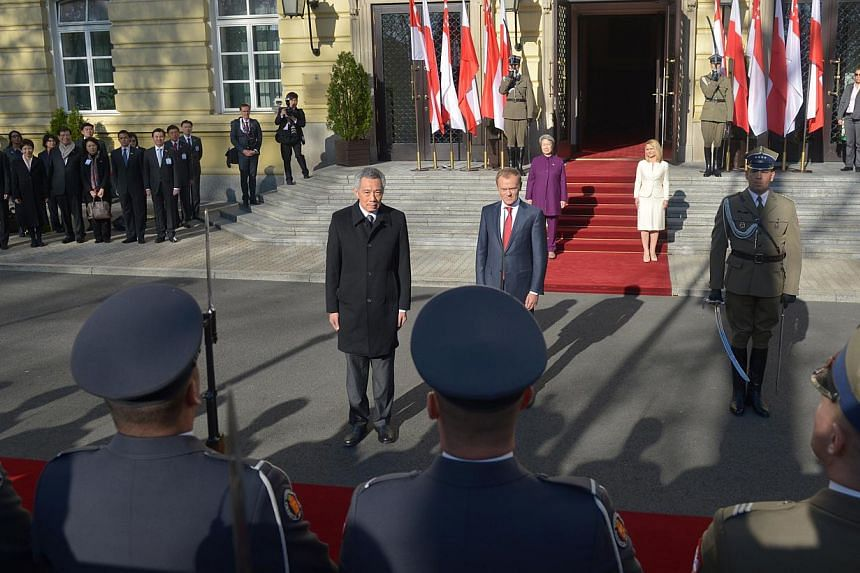 Prime Minister Lee Hsien Loong and Polish Prime Minster Donald Tusk (in dark blue suit) at the welcome ceremony held at the Chancellery of the Prime Minister, in Warsaw, on Oct 31, 2013. -- ST PHOTO: CAROLINE CHIA