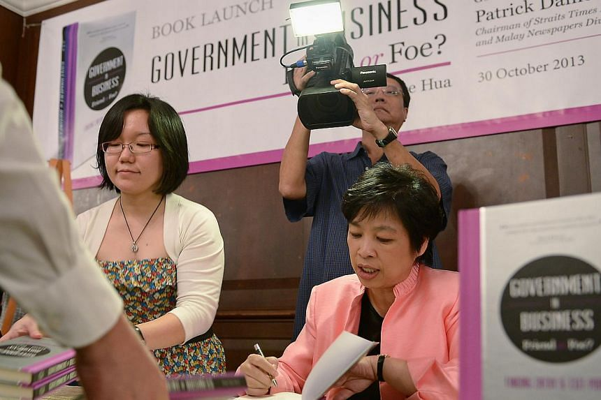 Former minister Lim Hwee Hua signing copies of her book, Government In Business: Friend Or Foe? at the Tanglin Club yesterday. Mrs Lim wrote the book following her departure from politics after the 2011 polls. -- ST PHOTO: NG SOR LUAN
