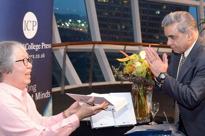 Professor Tommy Koh signing his book for Professor Kishore Mahbubani. The book, launched yesterday, contains insights into his career, his take on issues on diplomacy and law, and tributes to former presidents. -- ST PHOTO: LIM SIN THAI