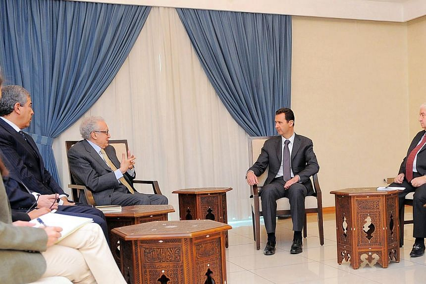 In this photo released by the Syrian official news agency Sana, Syrian President Bashar Assad, second right, meets with UN-Arab League envoy for Syria, Mr Lakhdar Brahimi, center, in Damascus, Syria, on Wednesday, Oct 30, 2013. -- PHOTO: AP