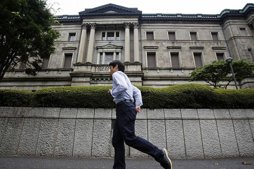 A pedestrian walks past the Bank of Japan headquarters in Tokyo on Aug 8, 2013.The Bank of Japan on Thursday held off launching fresh easing measures as evidence of an economic recovery piles up, a day after the US central bank left its own stimulus