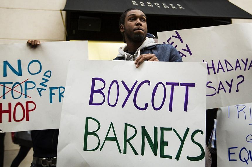 Demonstrators stand in front of a Barney's luxury department store of with signs decrying allegations that Barney's and Macy's stores have unfair security policies aimed at minorities in New York on Oct 30, 2013. -- PHOTO: REUTERS