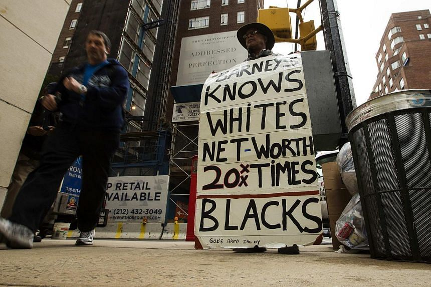 A man stands with a sign in protest of recent allegations that both Barney's and Macy's stores stopped minority shoppers for no apparent reason in New York on Oct 30, 2013. A small group of demonstrators gathered at the Manhattan storefront of Barney