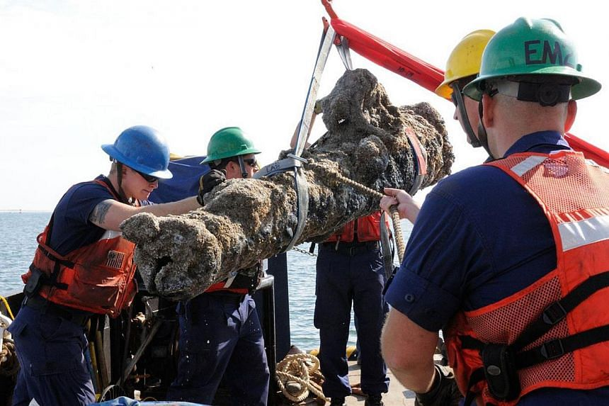 This photo courtesy of the North Carolina Department of Cultural Resources shows members of the US Coast Guard and others as they raise a cannon from a sunken ship on Oct 28, 2013 off the coast of North Carolina. Five large cannons from a sunken
