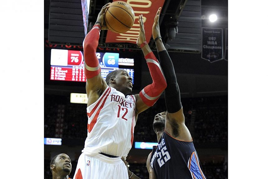 Houston Rockets' Dwight Howard (12) goes to the basket over Charlotte Bobcats' Al Jefferson (right) in the second half of an NBA basketball game on Wednesday, Oct 30, 2013, in Houston. Howard lived up to the hype on Wednesday, tying his career high w