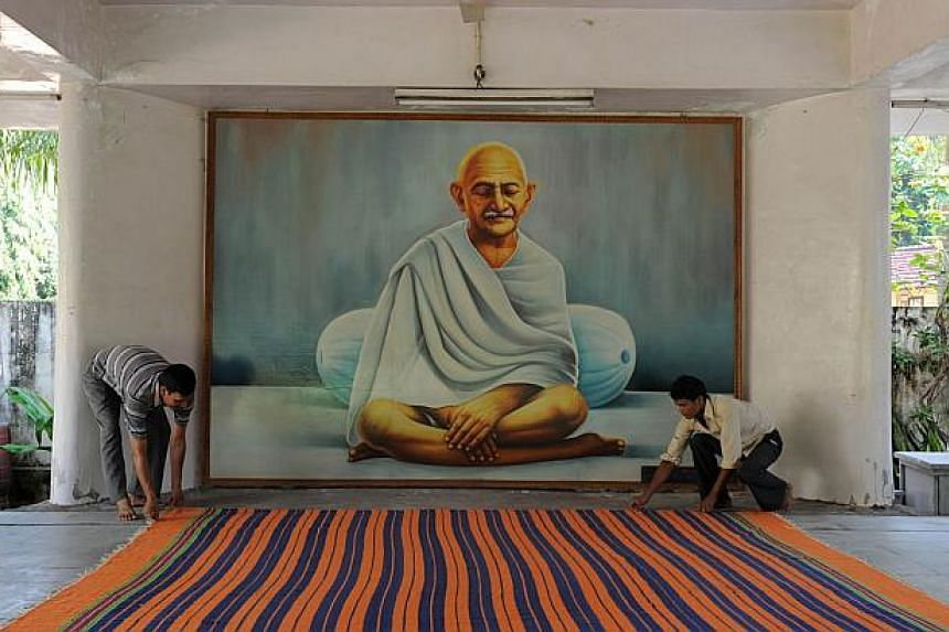 """In this photograph taken on Oct 11, 2013, caretaker, Mr Bhim Bahdur (left) spreads a carpet in the Prayer Hall at Kochrab Ashram, Mahatma Gandhi's most famous ashram and site of the """"Live Gandhi for a While"""" programme in Ahmedabad. -- PHOTO: AFP&nbsp"""
