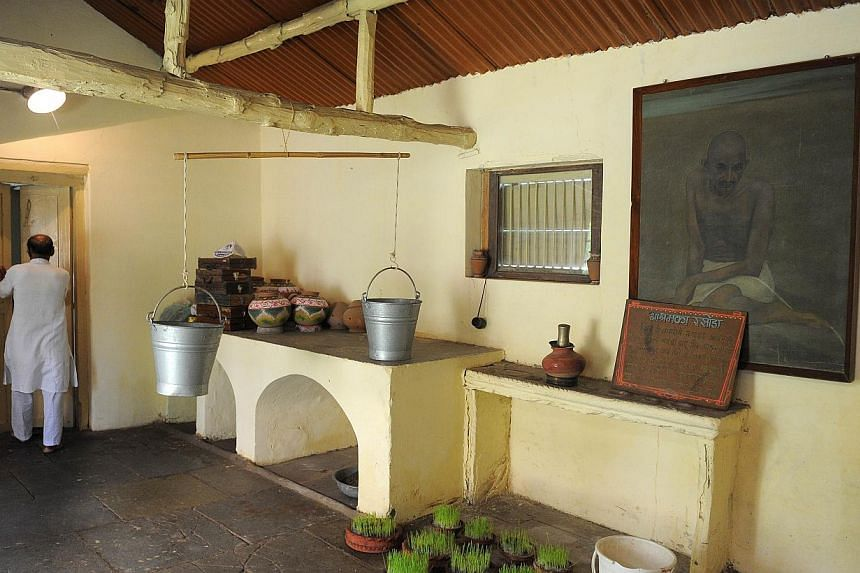 """In this photograph taken on Oct 11, 2013, ashram co-ordinator Rameshbhai Trivedi walks through the kitchen and dining area at Kochrab Ashram, Mahatma Gandhi's most famous ashram and site of the """"Live Gandhi for a While"""" programme in Ahmedabad. -- PHO"""