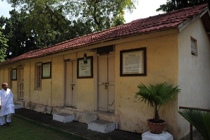 """In this photograph taken on Oct 11, 2013, ashram co-ordinator Rameshbhai Trivedi walks near the kitchen and dining hall at Kochrab Ashram, Mahatma Gandhi's most famous ashram and site of the """"Live Gandhi for a While"""" programme in Ahmedabad. -- PHOTO:"""