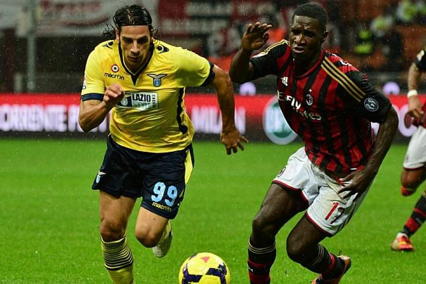 Lazio's forward Sergio Floccari (left) fights for the ball with AC Milan's Colombian defender Cristian Zapata during the Italian Serie A football match AC Milan vs Lazio at the San Siro Stadium in Milan on Oct 30, 2013. -- PHOTO: AFP