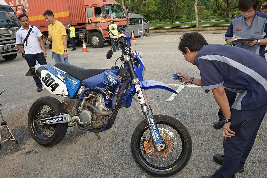An STA inspector checking the modification of the motor bike. -- ST PHOTO: DESMOND WEE