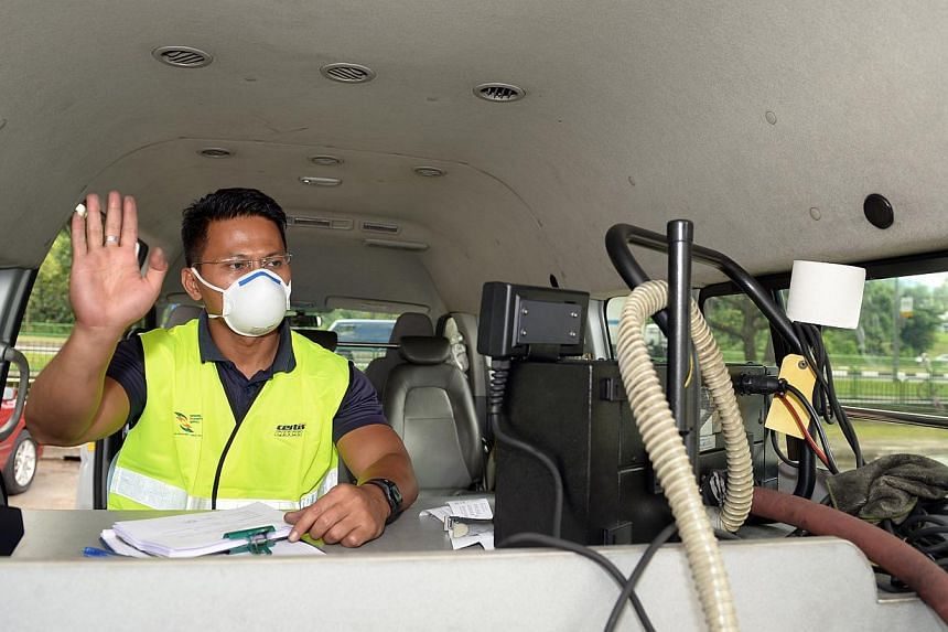 An NEA enforcement warden signaling and checking the carbon monoxide emission using a smoke meter that feed a hose to the exhaust pipe of a heavy vehicle. -- ST PHOTO: DESMOND WEE