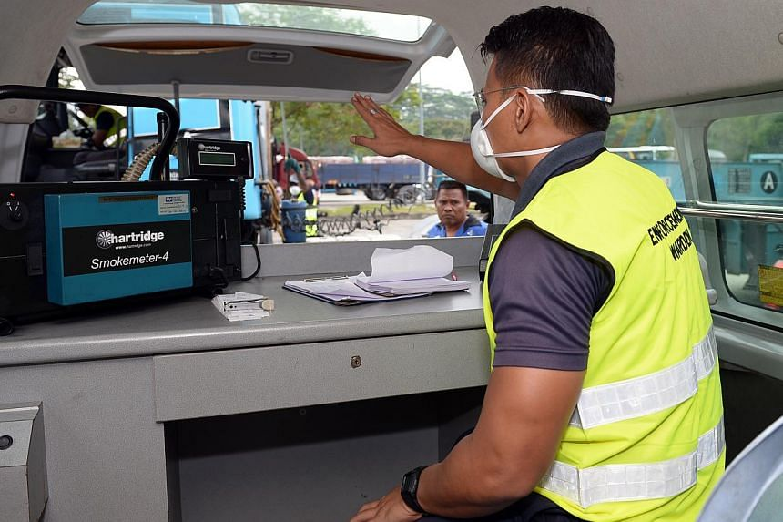 An NEA enforcement warden checking the carbon monoxide emission using a smoke meter that feed a hose to the exhaust pipe of a heavy vehicle. -- ST PHOTO: DESMOND WEE