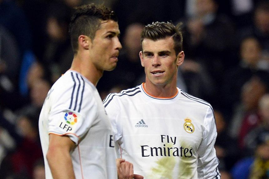 Real Madrid's Welsh striker Gareth Bale (right) congratules Real Madrid's Portuguese forward Cristiano Ronaldo at the end of the Spanish league football match Real Madrid CF vs Sevilla FC at the Santiago Bernabeu stadium in Madrid on October 30, 2013