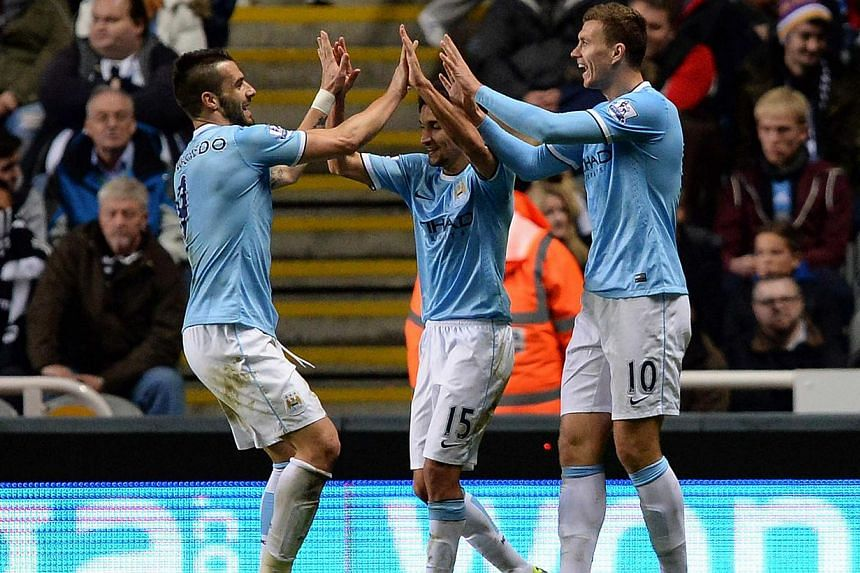 Manchester City's Edin Dzeko (right) celebrates scoring with Jesus Navas (centre) and Alvaro Negredo during their English League Cup fourth round soccer match against Newcastle United at St James' Park in Newcastle, on Oct30, 2013. -- PHOTO: REUTERS&