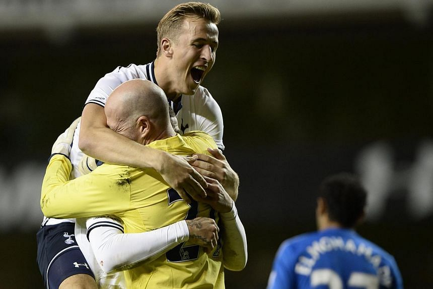 Tottenham Hotspur's Harry Kane (top) celebrates beating Hull City in a penalty shoot out with Kyle Walker and Brad Friedel (front left) during their English League Cup fourth round soccer match at White Hart Lane in London, on Oct 30, 2013. -- PHOTO: