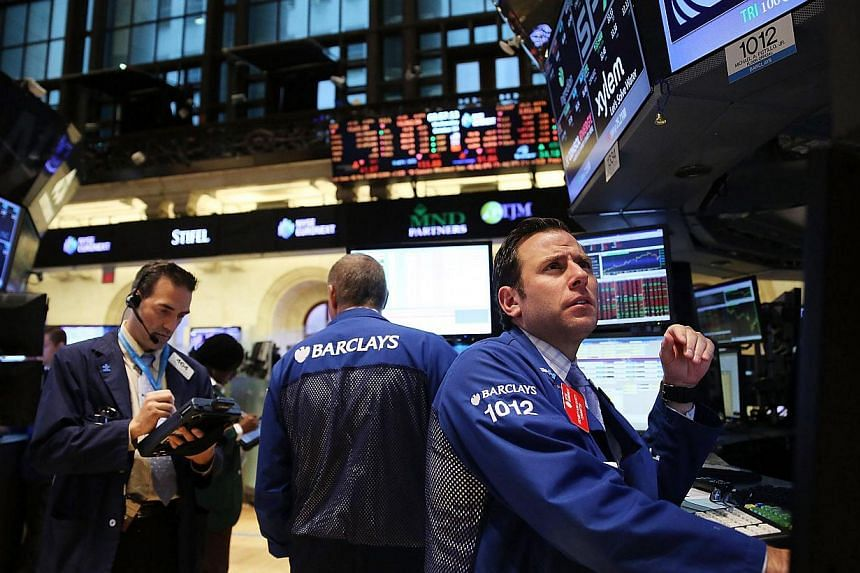 Traders work on the floor of the New York Stock Exchange at the end of the trading day on Oct 30, 2013 in New York City. The Federal Reserve extended its support for a soft United States (US) economy on Wednesday, sounding a bit less optimistic about