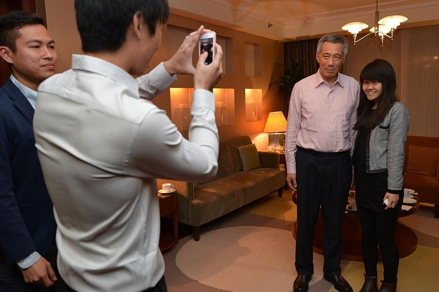 Ms Nadine Ng, 20, an NUS student currently on an exchange with Warsaw School of Economics, takes a photo with PM Lee. -- ST PHOTO: CAROLINE CHIA