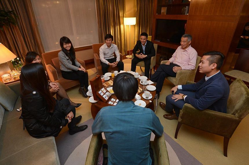 PM Lee Hsien Loong having tea with seven Singaporean students at the Hyatt Hotel in Warsaw on Oct 30, 2013. -- ST PHOTO: CAROLINE CHIA