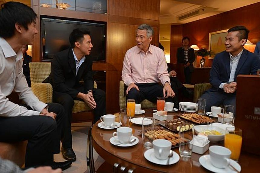 PM Lee Hsien Loong chatting with university students, (from left) Shannon Chan, Swenson Chen, and Tan Shing Kwan. -- ST PHOTO: CAROLINE CHIA