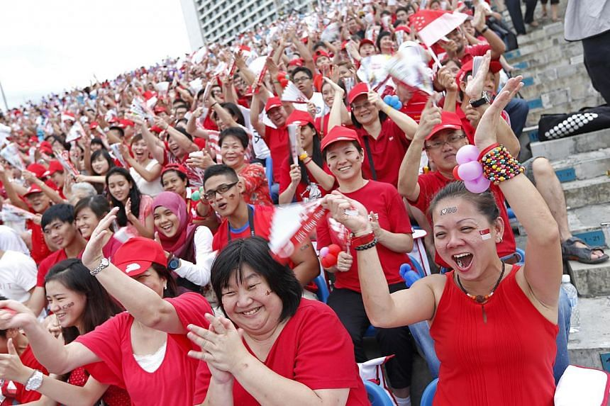 Audience members cheering at this year's National Day Parade. -- ST PHOTO: DESMOND LUI