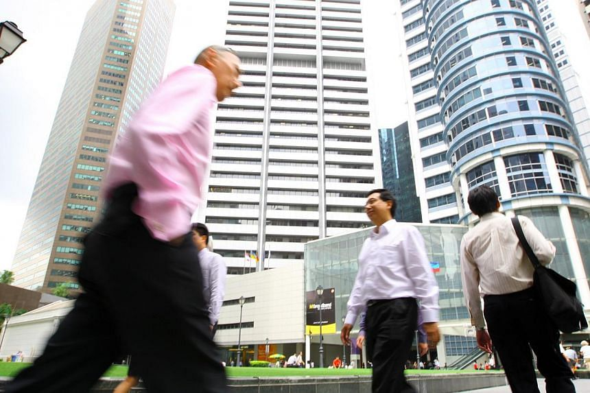 Office workers at Raffles Place.Fewer jobs are being created but employers are still hungry for workers, according to latest official figures. -- ST FILE PHOTO:ALAN LIM