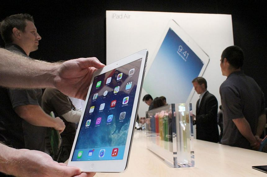 An Apple employee holds up the new iPad Air at a launch event in San Francisco, California. Singapore telcos have announced their price plans for the long-awaited iPad Air, which launches here on Nov 1, 2013. -- ST FILE PHOTO: DERRICK HO