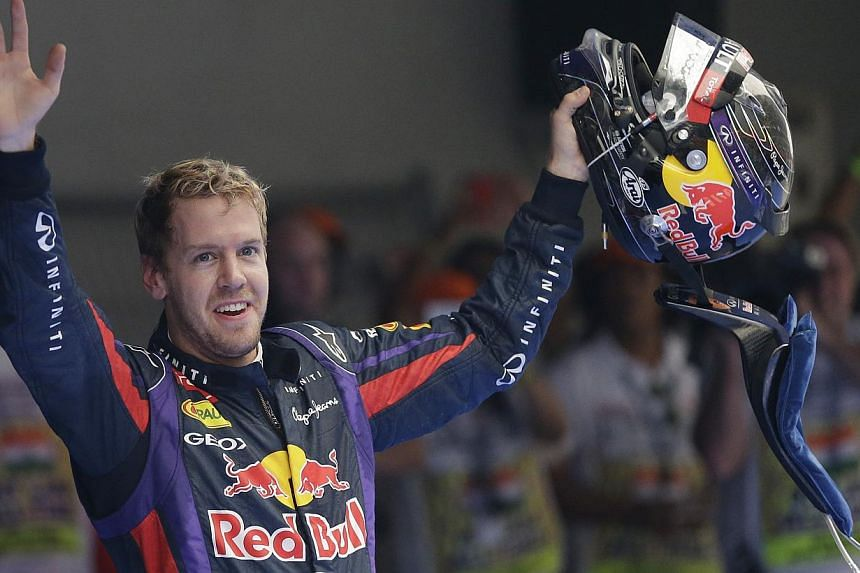 Red Bull driver Sebastian Vettel of Germany waves to the crowd after winning the Indian Formula One Grand Prix and his fourth straight F1 world drivers championship at the Buddh International Circuit in Noida, India, on Oct 27, 2013.Vettel's id