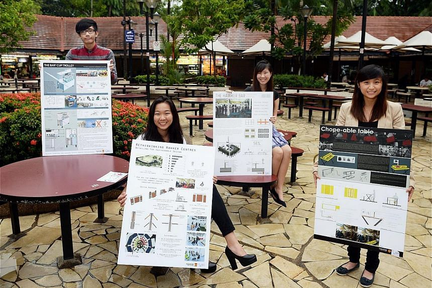 Poly students here seen holding up boards showcasing some of the design ideas they have proposed for the hawker centre of the future. The NEA approached students from Singapore Poly's School of Architecture and the Built Environment to help tackle lo