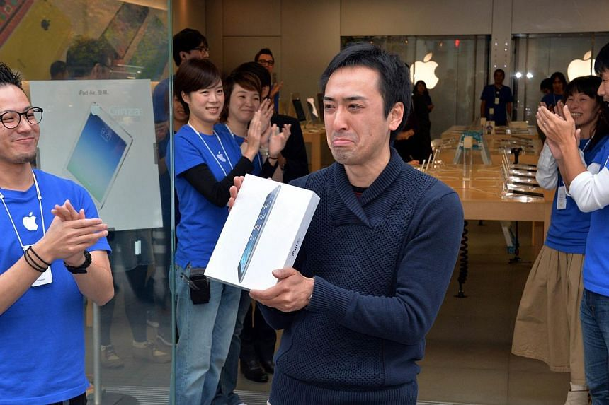 An Apple store's first customer of the day displays a package containing Apple's new iPad Air tablet in Tokyo on Friday, Nov 1, 2013.For Mr Takaaki Sasak, being at the front of a Tokyo queue as the new iPad debuted around the world was his way