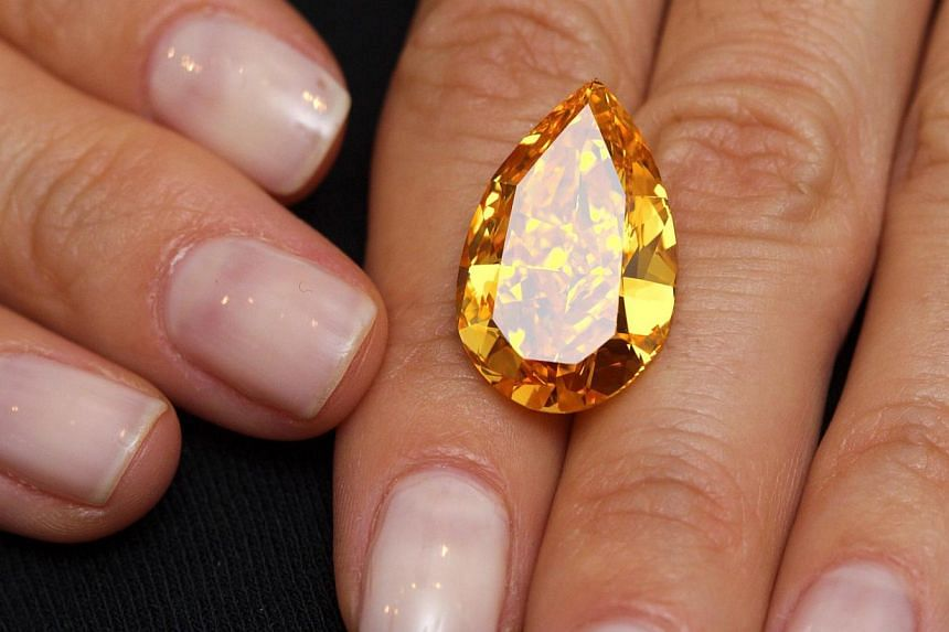A Christie's member of staff displays The Orange,the largest fancy vivid orange diamond in the world, which weighs 14.82 carats during an auction preview in Geneva on Friday, Nov 1, 2013.-- PHOTO: REUTERS