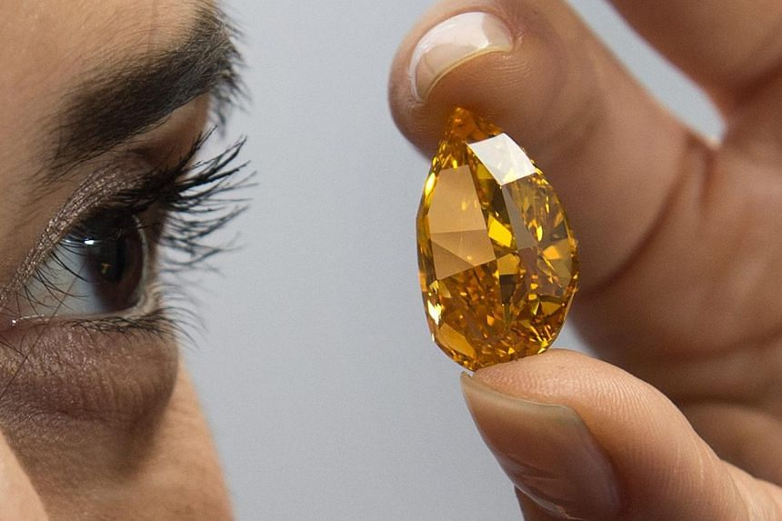 A Christie's employee displays The Orange,the largest fancy vivid orange diamond in the world, during a press preview in Geneva, Switzerland on Friday, Nov 1, 2013. -- PHOTO: AP