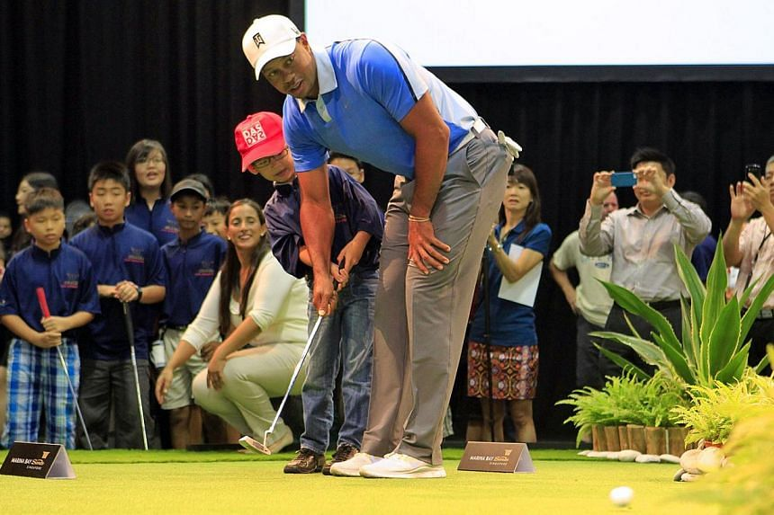 World number one golfer Tiger Woods guides seven-year-old Chua Jin Sen (red cap), better known as Singapore's YouTube sensation Dr Jiajia, with a putt during a golf clinic at Marina Bay Sands Expo and Convention Centre, on Friday, Nov 1, 2013. -- ST