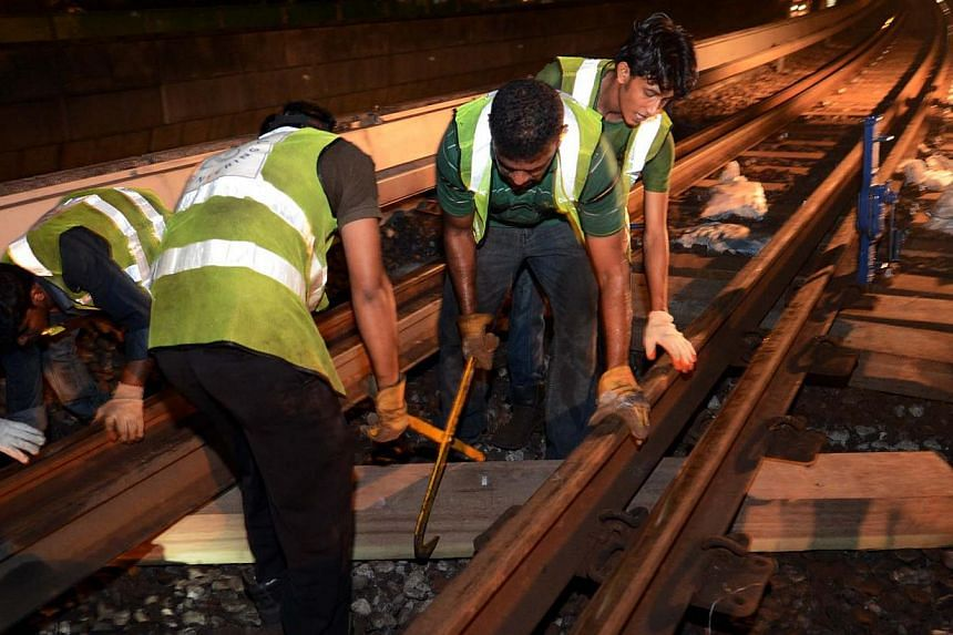 "Maintenance staff replacing the wooden sleepers on the train tracks near Clementi MRT station. A Land Transport Authority spokesman said ""speed restrictions are temporarily imposed on sections of the track where sleepers have been recently"