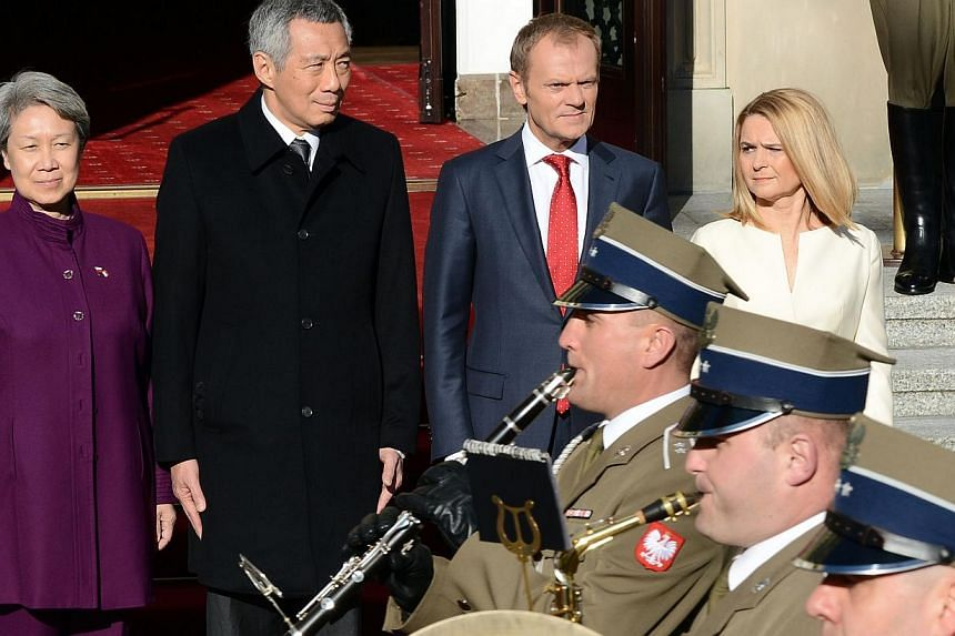 Singapore's Prime Minister Lee Hsien Loong (2nd left) and his wife Ho Ching (left), accompanied by Polish Prime Minister Donald Tusk (2nd) and his wife Malgorzata (right), receive military honours at the beginning of their meeting in Warsaw on Oct 31