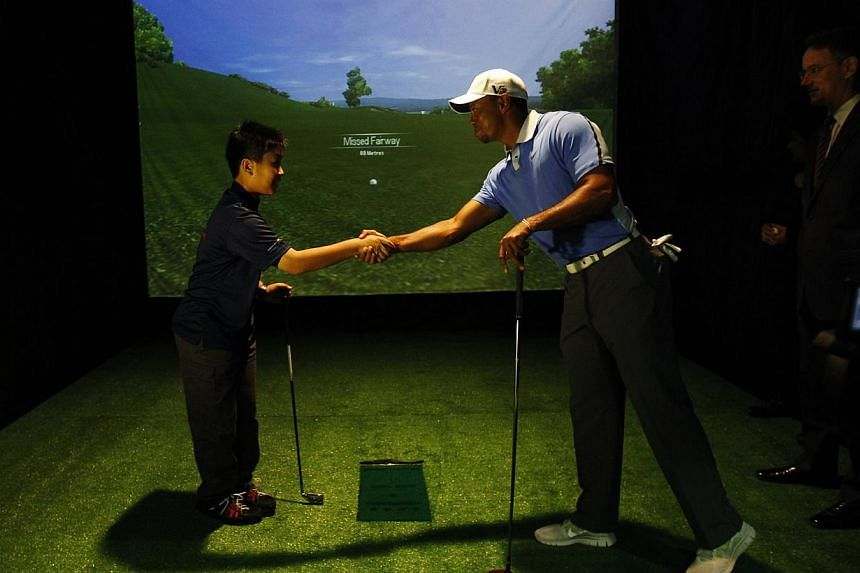 US golfer Tiger Woods shakes hands with a boy after a tee-off at a golf simulator during an event to meet with young athletes in Singapore on Nov 1, 2013. Woods on Friday met with student athletes from the Singapore Sport School, Golf Academy and the