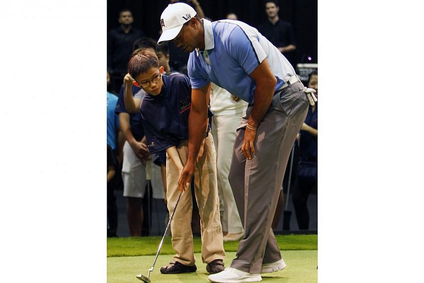 US golfer Tiger Woods guides a boy as he putts on a hole during an event to meet with young athletes in Singapore on Nov 1, 2013. Woods on Friday interacted with student athletes from the Singapore Sport School, Golf Academy and the Dyslexia Associat