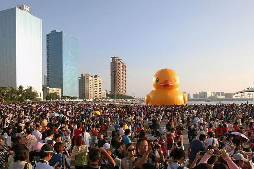 Local residents gahter to see Dutch artist Florentijn Hofman's yellow rubber duck (centre) at a harbour in the southern city of Kaohsiung on Sept 19, 2013.A giant yellow duck on display in Taiwan became a high-profile victim of recent earthquak