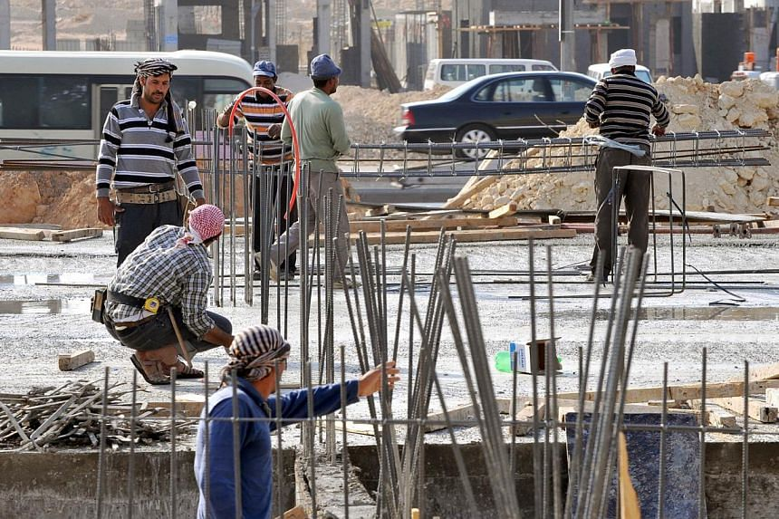 Foreign labourers work at a construction site in the Saudi capital Riyadh in this Oct 30, 2013 file photo. Oil-rich Saudi Arabia, a magnet for mostly poor Asian foreign workers, has seen nearly a million illegal workers quit, taking advantage of a si