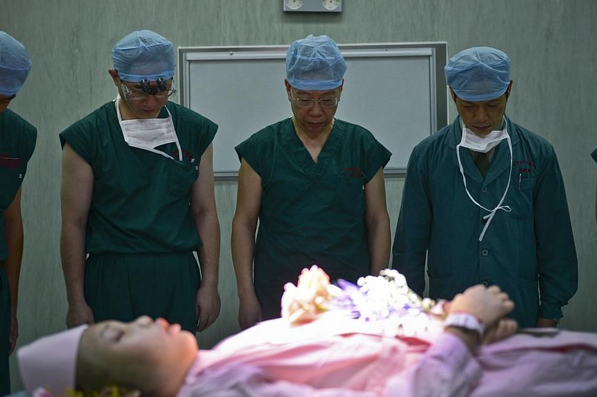 Then deputy health minister Huang Jiefu (centre) and his colleagues bow as they pay a silent tribute to a deceased patient who was willing to donate her organs, at a hospital in Guangzhou, Guangdong province, in this Nov 22, 2012, file photo. China p