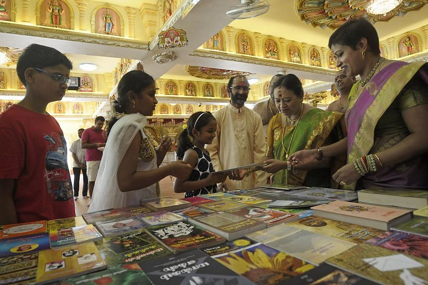 Sree Maha Mariamman Temple president Kalyani Ramasamy (second from right) and CEO Parvathi Annanth (right) with some of the books the temple will give out today as part of the festivities. -- PHOTO: JOSEPH NAIR FOR THE STRAITS TIMES