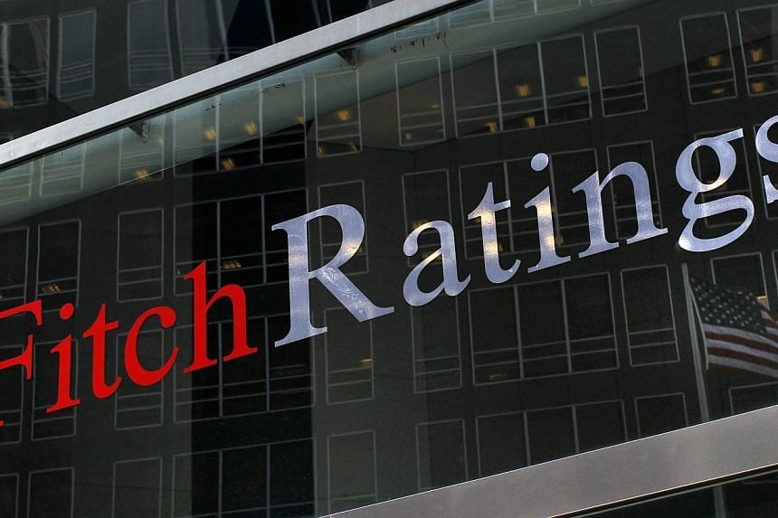 """A flag is reflected on the window of the Fitch Ratings headquarters in New York in this Feb 6, 2013, file photo. Fitch Ratings said Friday it was upgrading Spain's outlook to """"stable"""" thanks to progress in reforms and improved export performance, and"""
