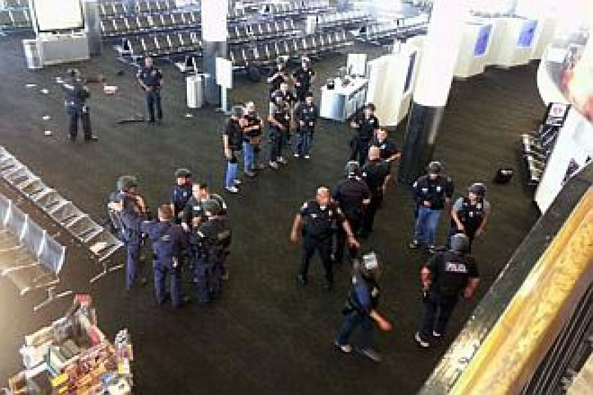 In this photo provided to the AP, which has been authenticated based on its contents and other AP reporting, police officers stand near an unidentified weapon in Terminal 3 of the Los Angeles International Airport on Friday, Nov 1, 2013. -- PHOTO: AP