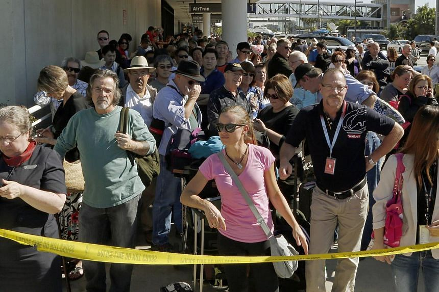 Passengers evacuated from Terminal 1 wait outside Los Angeles International Airport on Friday, Nov 1, 2013. -- PHOTO: AP