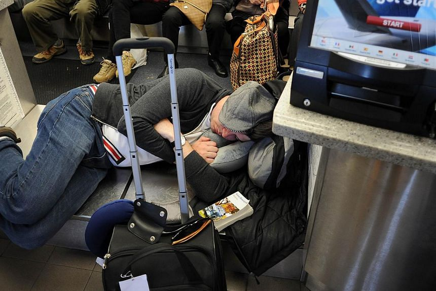 A man sleeps on a baggage scale at the check-in counter after a shooting incident at Los Angeles International Airport (LAX) on Nov 1, 2013, after a gunman reportedly opened fire at a security checkpoint. -- PHOTO: AFP