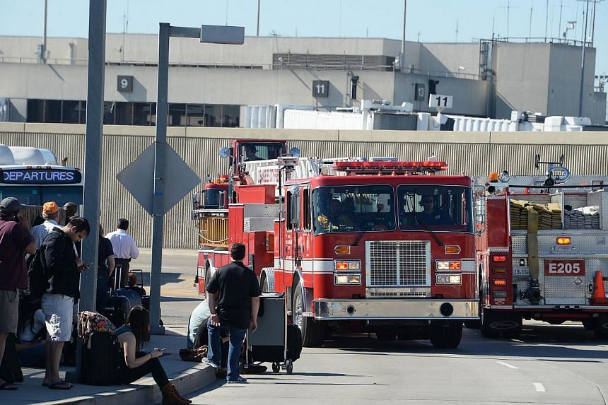 Delayed passengers watch for the roadside and fire trucks go in and out of the airport after a shooting incident at Los Angeles airport Los Angeles International Airport on Nov 1, 2013 after a gunman opened fire with an assault rifle, killing a secur